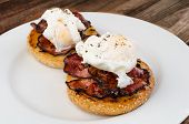 pic of benediction  - Benedict eggs with crispy bacon and hollandaise sauce on toasted Maffin on clean plate - JPG
