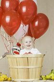 stock photo of sock-monkey  - An infant boy sitting in a wooden basket with balloons and a sock monkey - JPG