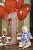pic of sock-monkey  - An infant boy sitting among balloons and a sock monkey for his birthday - JPG