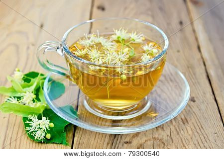 Herbal tea of linden flowers in glass cup on board