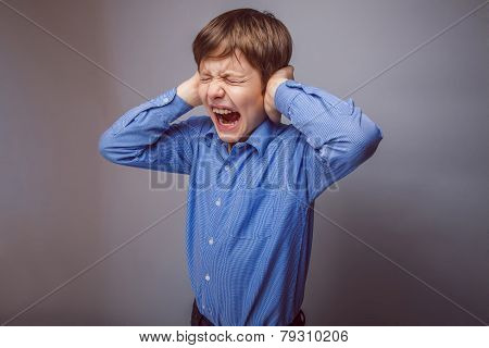 boy teenager yells covers ears closed his eyes on gray bac