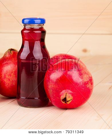 Bottle of pomegranate juice with pomegranates.