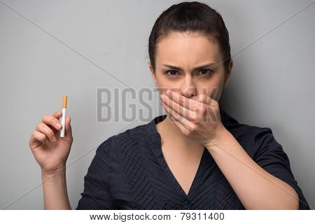 Addiction. Closeup of young woman determined girl holding cigare