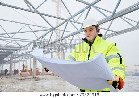 male engineer construction foreman manager outdoors indoors at building site with blueprints