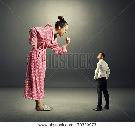 small serious man in black suit looking at big angry woman in pink dressing gown. photo over dark background