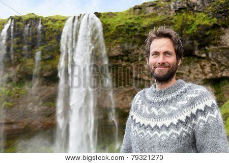 Man in Icelandic sweater by waterfall on Iceland. Bearded male portrait of good looking guy in his 30s in nature landscape with tourist attraction Seljalandsfoss waterfall on Ring Road.