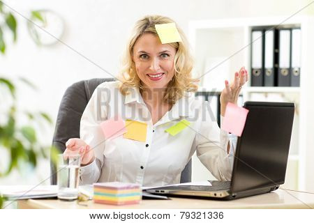 businesswoman overwhelmed with sticky reminder notes