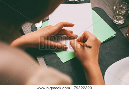 Woman Writing Contract In Cafe