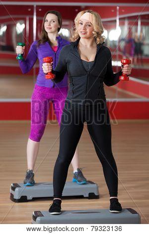 Girls On The Step Board Lift Dumbbells
