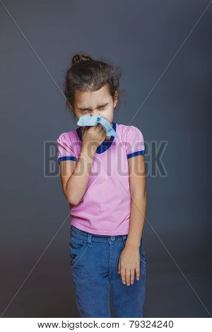 girl blows her nose wrinkled and a handkerchief