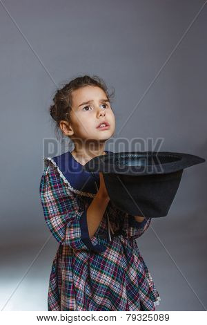 girl child beggar holding hat on a gray background