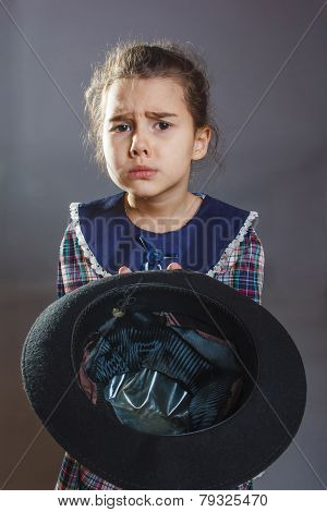 girl child beggar just money keeps his hat on a gray background