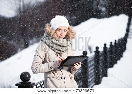 Woman On The Tablet Smartphone In Winter Park On A Background Of The River. Multi-ethnic Girl Smiles