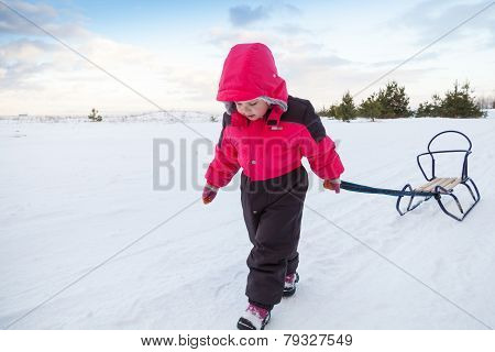 Little Baby Girl In Pink Pulling A Sled On Snowy Winter Road