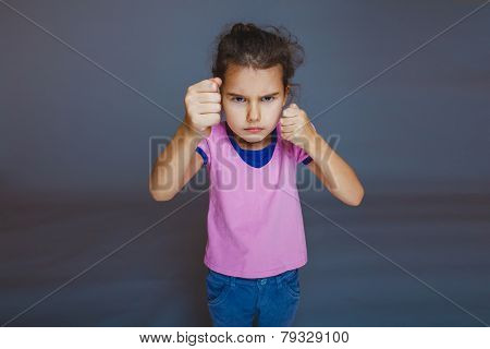 girl clenched her fists on a gray background
