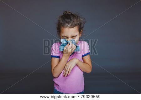 girl closed her eyes and blowing his nose into a handkerchief