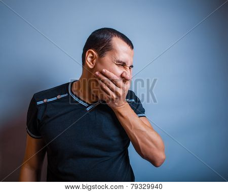 years old man of European appearance yawning on gray backgrou
