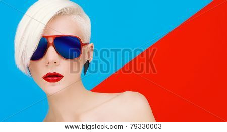 Fashion Blond Model With Trendy Haircut And Sunglasses On Bright Background