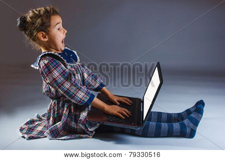 girl looking at a computer is experiencing vivid emotions