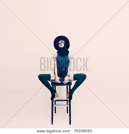Sensual Lady In A White Room Sitting On A Chair. Loneliness And Glamor Style