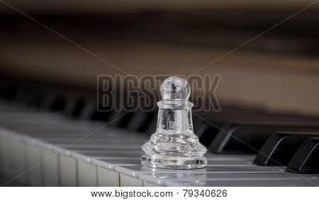 Glass chess pawn on the piano (shiny)