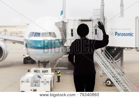 Silhouette Of A Woman Waving Goodbye To An Airplane