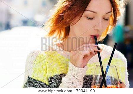 Young Woman Enjoying A Drink On A Sunny Day