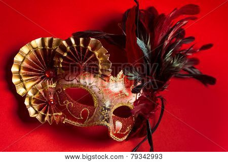 A red and gold venetian, mardi gras mask on a red background