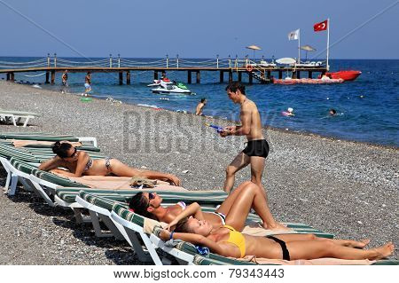 Boys And Girls Sunbathing On Pebbly Beach Resort Of Antalya.