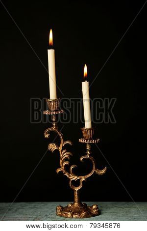 Retro candlestick with candles on wooden table, on black background