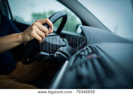 Male driver's hands driving a car on a highway (color toned image; shallow DOF)