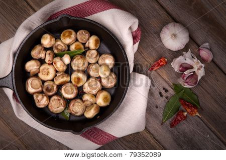 Button mushrooms with garlic, fried in a cast iron skillet, resting on a tea towel over an old wood background.