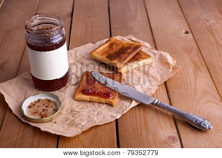 Toast bread spread with jam on piece of paper with knife near jar on wooden table background