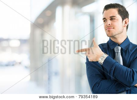 Smiling businessman pointing his finger to the copy-space