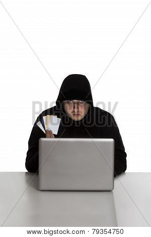 Hacker With Credit Cards On Silver Laptop