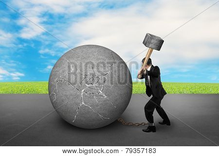 Businessman Holding Hammer Hitting Cracked Concrete Ball With Sky Clouds