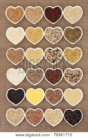 Grain and cereal food selection in heart shaped porcelain bowls over hessian background.
