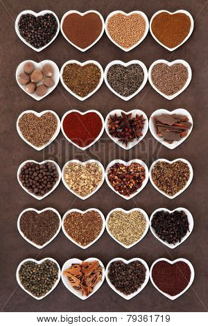 Large spice selection in heart shaped dishes over lokta paper background.