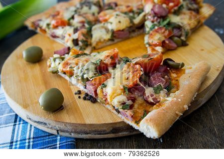 Chopped Pieces Of Pizza With Mushrooms, Olives And Salami