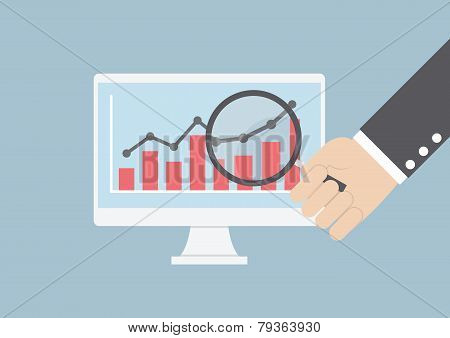 Businessman Hand Holding Magnifying Glass Focusing On Business Graph In Monitor