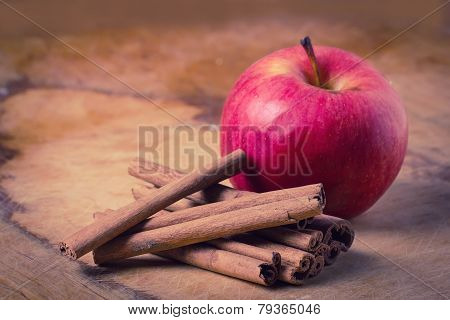 Cinnamon And Apple On Wooden Background.
