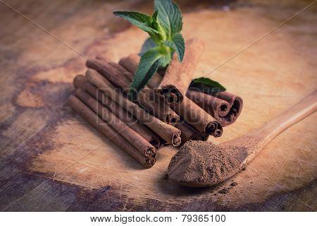 Cinnamon On Wooden Background.