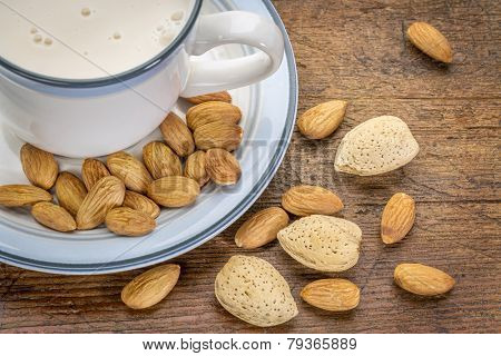 a cup of almond milk with almond nuts on a rustic barn wood table