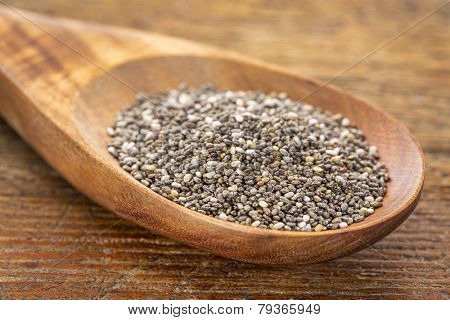 chia seeds on a wooden spoon against a grunge wood, selective focus
