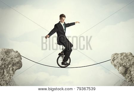 Brave business man riding an mono cycle between cliffs concept