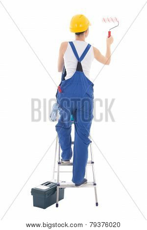 Back View Of Young Woman Painter In Blue Coveralls Standing On Ladder Isolated On White