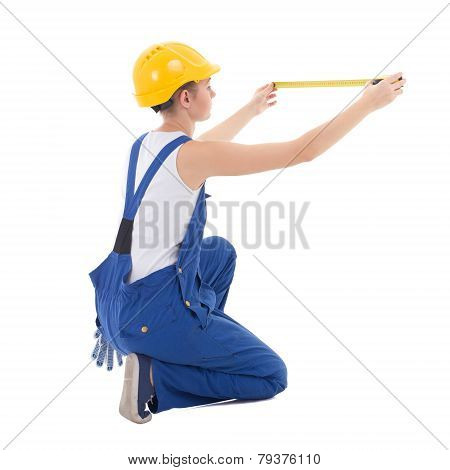 Back View Of Sitting Woman Builder In Workwear Measuring Something With Measure Tape Isolated On Whi