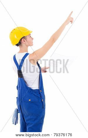 Back View Of Woman Builder In Blue Coveralls Holding Building Scheme And Showing Something Isolated