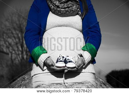 Pregnant Woman Sitting With Baby Shoes In Front Of Herself