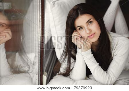Portrait of a young woman lying in bed at the window.